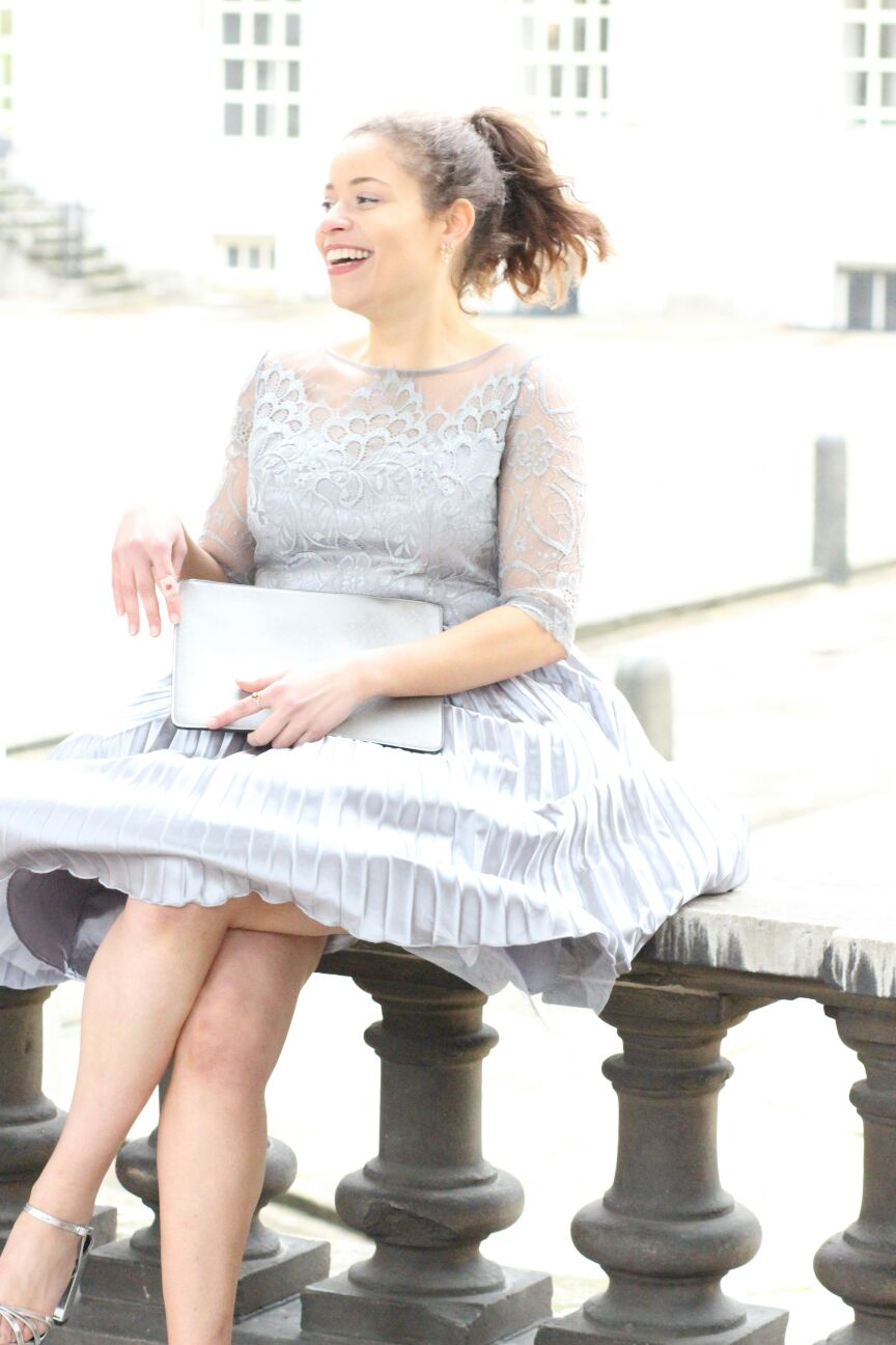 "Image of Eboni sitting and laughing, wearing the ""Hilary"" dress by Chi Chi London."