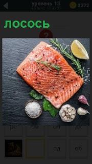 Приготовление универсального продукта филе лосося на столе с чесноком и солью, зеленью рядом