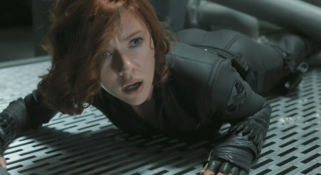 Scarlett Johansson lying down in her black catsuit in The Avengers 2012 movieloversreviews.filminspector.com