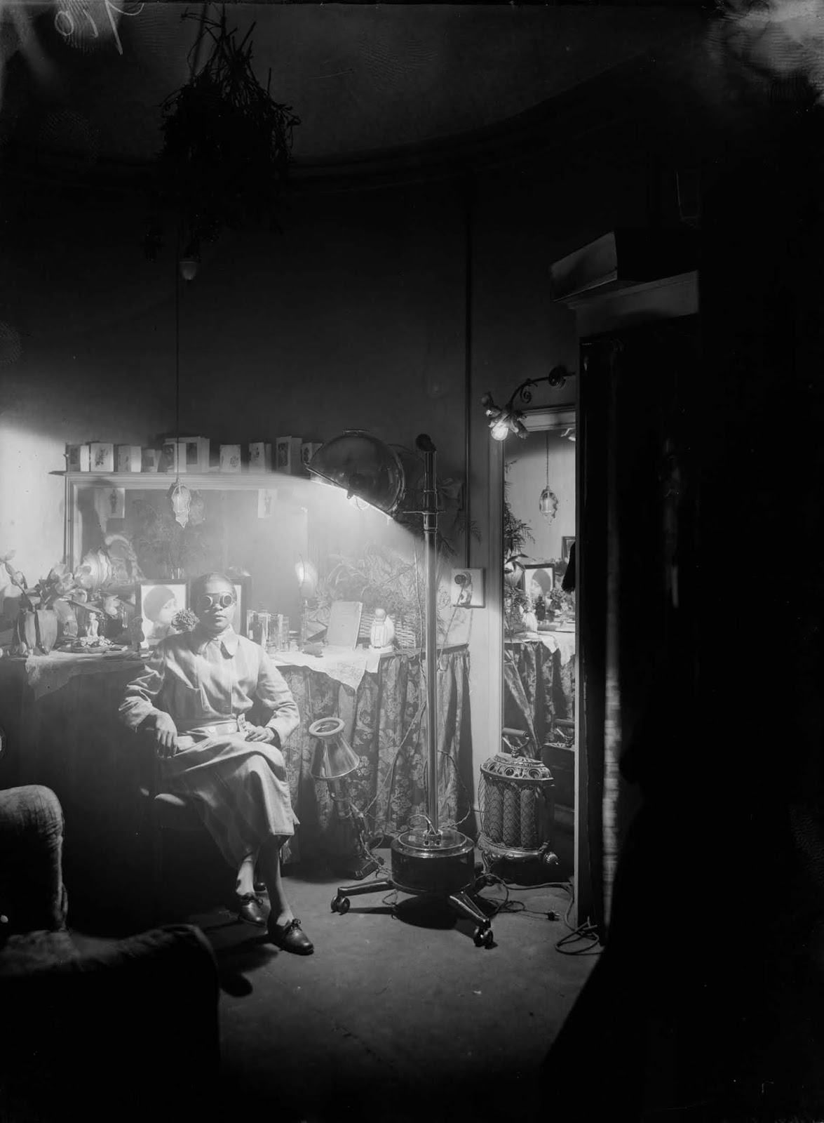 American comedienne Florence Mills basks in the glow of a sun lamp in her dressing room. 1925.