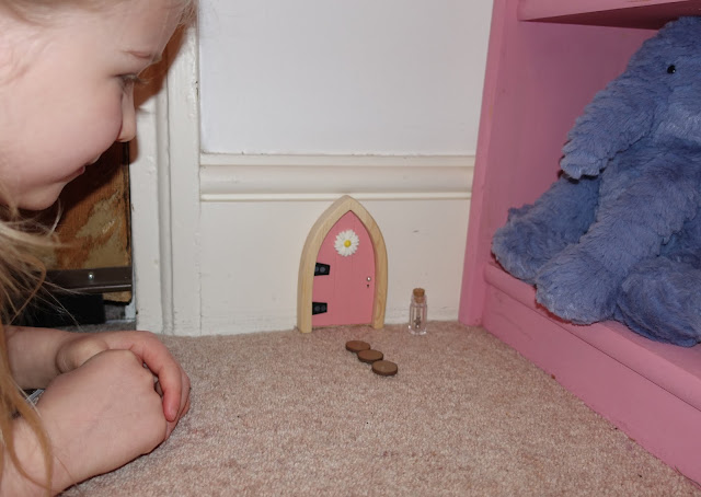 A girl on the floor peering at a pink fairy door, with stepping stones and a key from the Irish Fairy Door Company