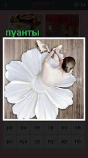 балерина на полу одевает пуанты для своего танца