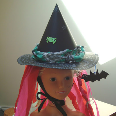 A witches hat made out of two sheets of A3 card and decorated with crepe paper, white pencil, sticker and fabric scraps by Amanda Lillywhite