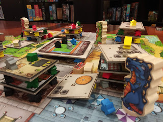 A similar view of the board, this time from the point of view of the blue monster with the green and red monsters visible in the background. However, this time, some of the cardboard 'floors' of the buildings have been knocked off the stack onto the board, and the meeples have likewise been knocked around.