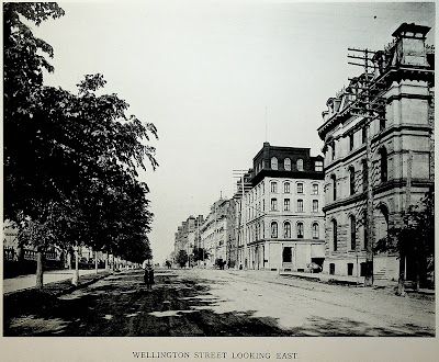 Photo taken from Wellington Street, looking east, at around O'Connor Street, with the street extending into the horizon. From left to right: The stone and wrought iron fence at the perimeter of Parliament Hill, the north sidewalk (material unclear), a boulevard planted with a continuous row of trees, the roadway which is dirt and rutted, a bicyclist in the road heading straight toward the camera, a horse drawn carriage further away on the opposite side of the street, telephone poles each with nine rows of eight insulators, the south sidewalk (concrete?) with some trees, buildings on the south side of Wellington Street, all around 4 storeys tall. The photo has an all-caps caption at the bottom (from the book from which it was scanned), Wellington Street Looking East