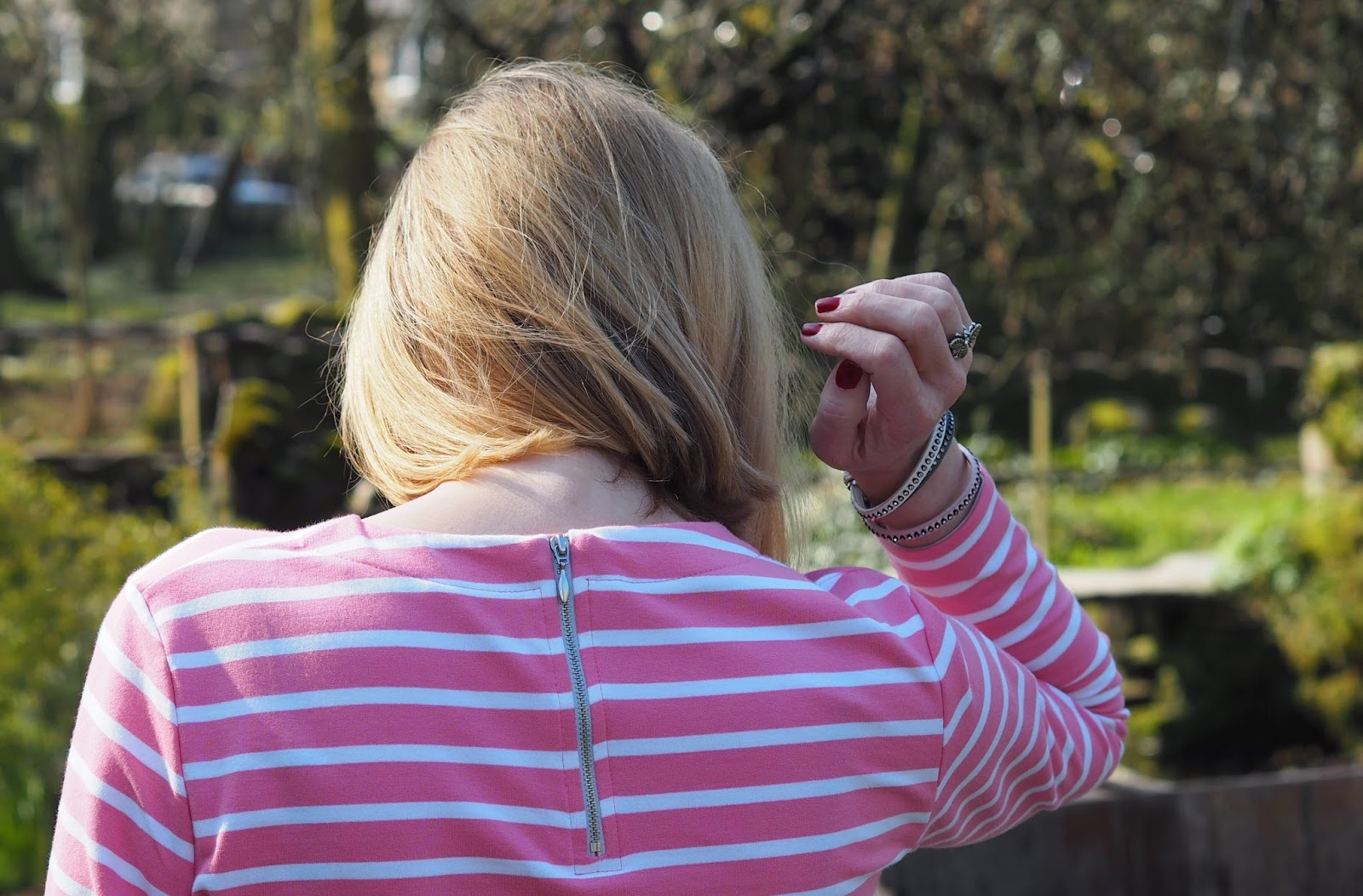 Back view of pink and white striped breton top by Tulchan with skinny jeans and silver Superga pumps