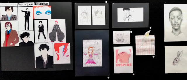 "A collection of paintings and drawings displayed in one section of the exhibition. The works are on white paper, most of them in pencil or charcoal. On the left hand side are paintings which use solid blocks of colour to depict modern pop identities like Robert Smith of The Cure and David Bowie and called ""Idol""."