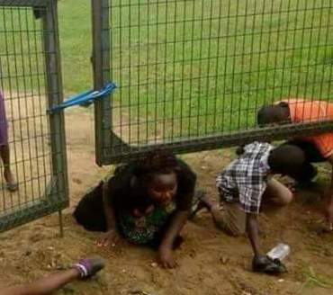 Children pictured sneaking through opening under their school gate in Port Harcourt over alleged forced vacination by army