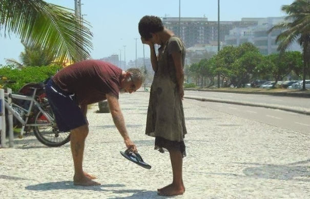 A man gives his shoes to a homeless girl in rio de janeiro.