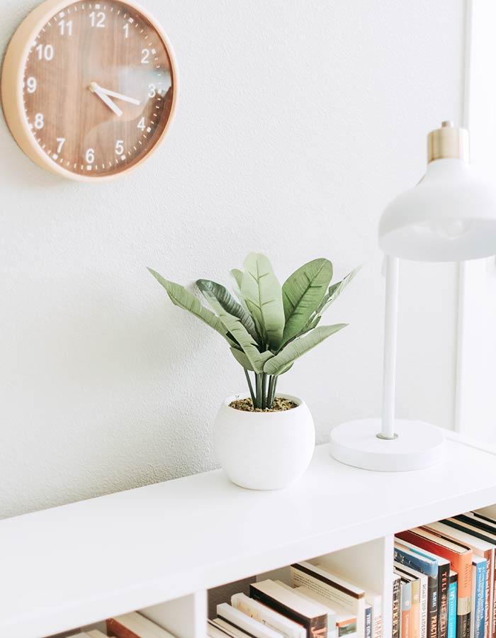 Planta ornamental artificial na decoração da estante de livros; ficou um charme com a abajour moderna e o relógio de madeira na parede.