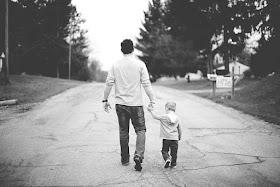 Vater und Sohn gehen Hand in Hand die Straße entlang