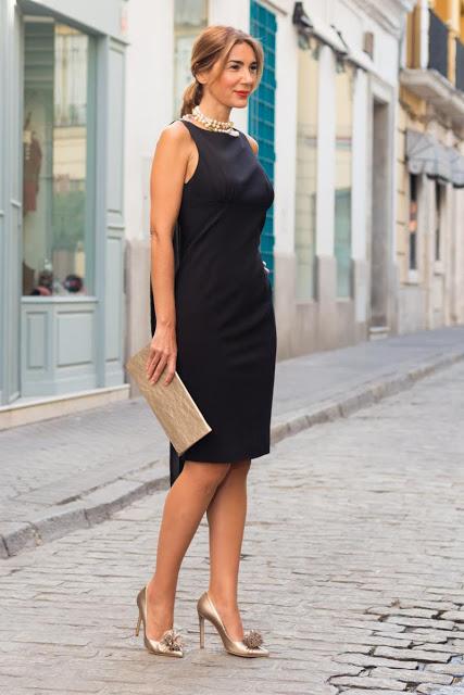 1fa98116b Nuria combina el negro de este vestido de Amparo Soriano con sus stilettos  Estrellas oro y cartera Dalia a juego.