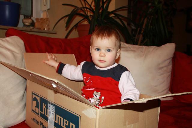 Kleinkind sitzt in einem Karton