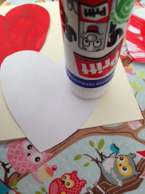 Glue stick gluing the back of the hearts