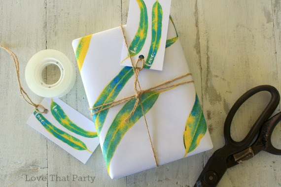 image of gift wrapped in nature leaf paper and string twine with scissors and tape