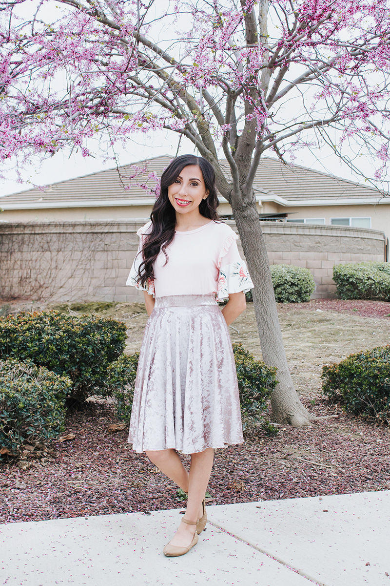 blush top with flounces and velvet skirt with floral tree background