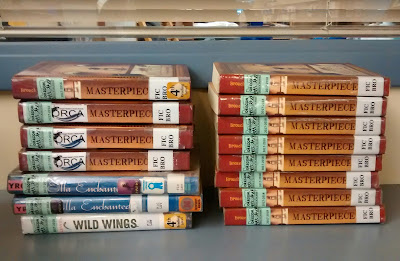 Two stacks of books, their spines facing viewer. Library call numbers are affixed to the books' spines, as are other labeling, including green labels designating them 2017-2018 selections in the Oregon Battle of the Books