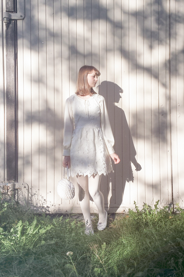 a girl in white outfit in the evening sun, casting a shadow on the wall