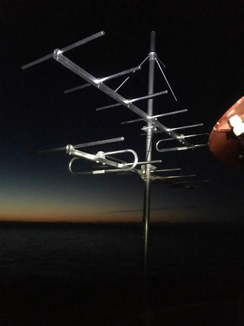 Antenni pimeydessä, taustalla auringonnousu.