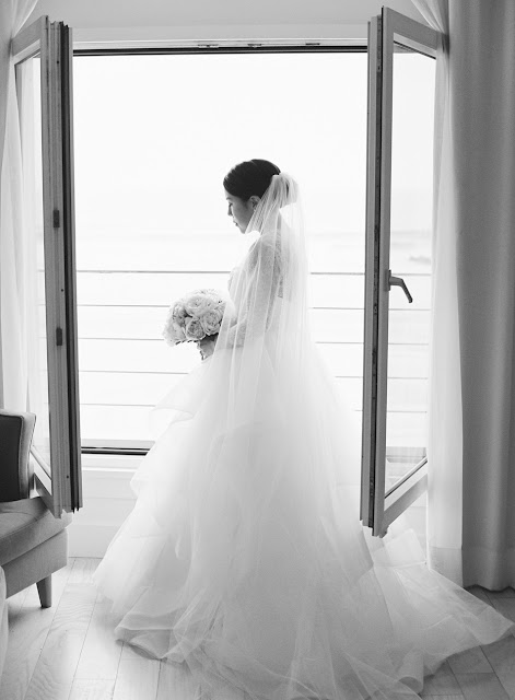 A portrait of Jin by the window in her wedding gown with pink and white bridal bouquet