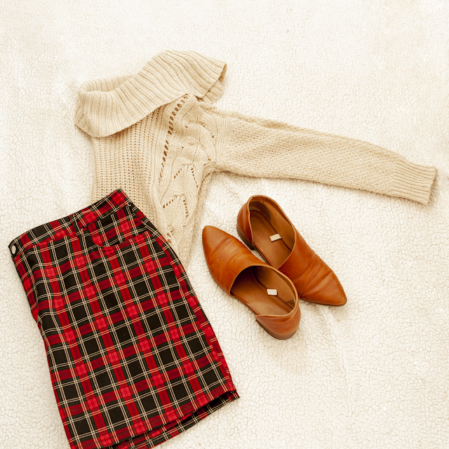 A flatlay of a cream cowl neck sweater, a red and black plaid mini skirt and brown d'orsay flats.