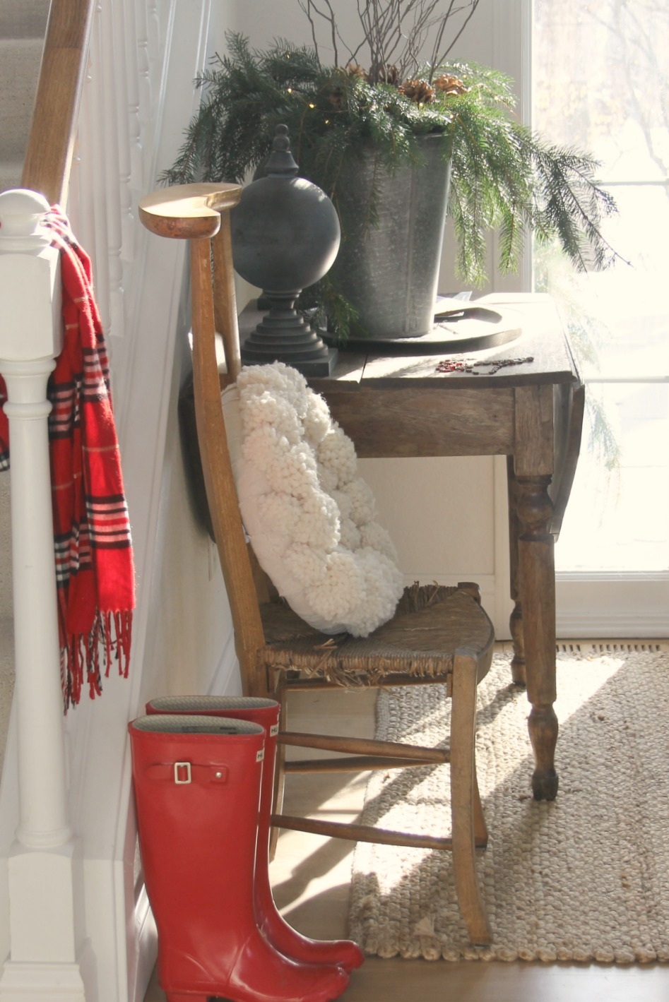 Christmas decor in entry with red plaid scarf, red boots, zinc vase, and pom pom wreath - Hello Lovely Studio