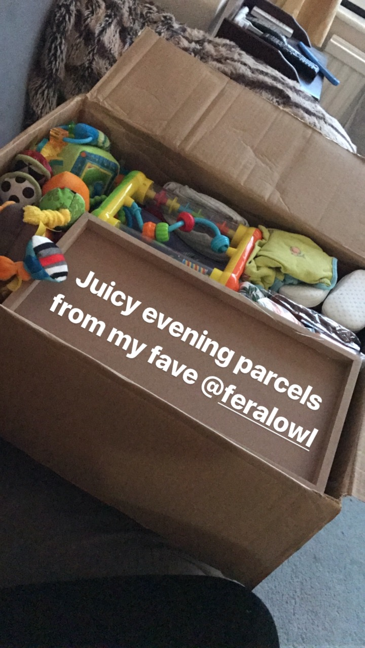 box of baby clothes and toys