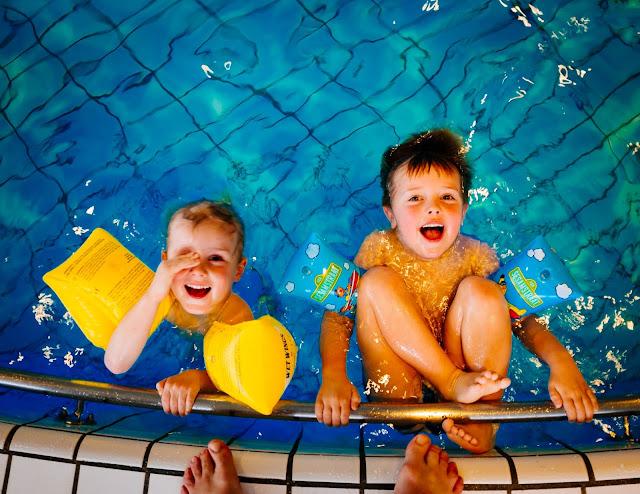 Niños en una piscina vigilados por un tutor