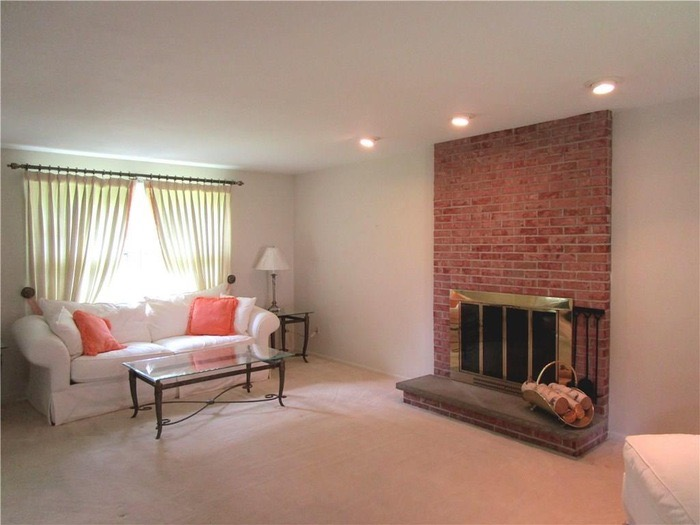 white carpeted living room with floor to ceiling brick fireplace