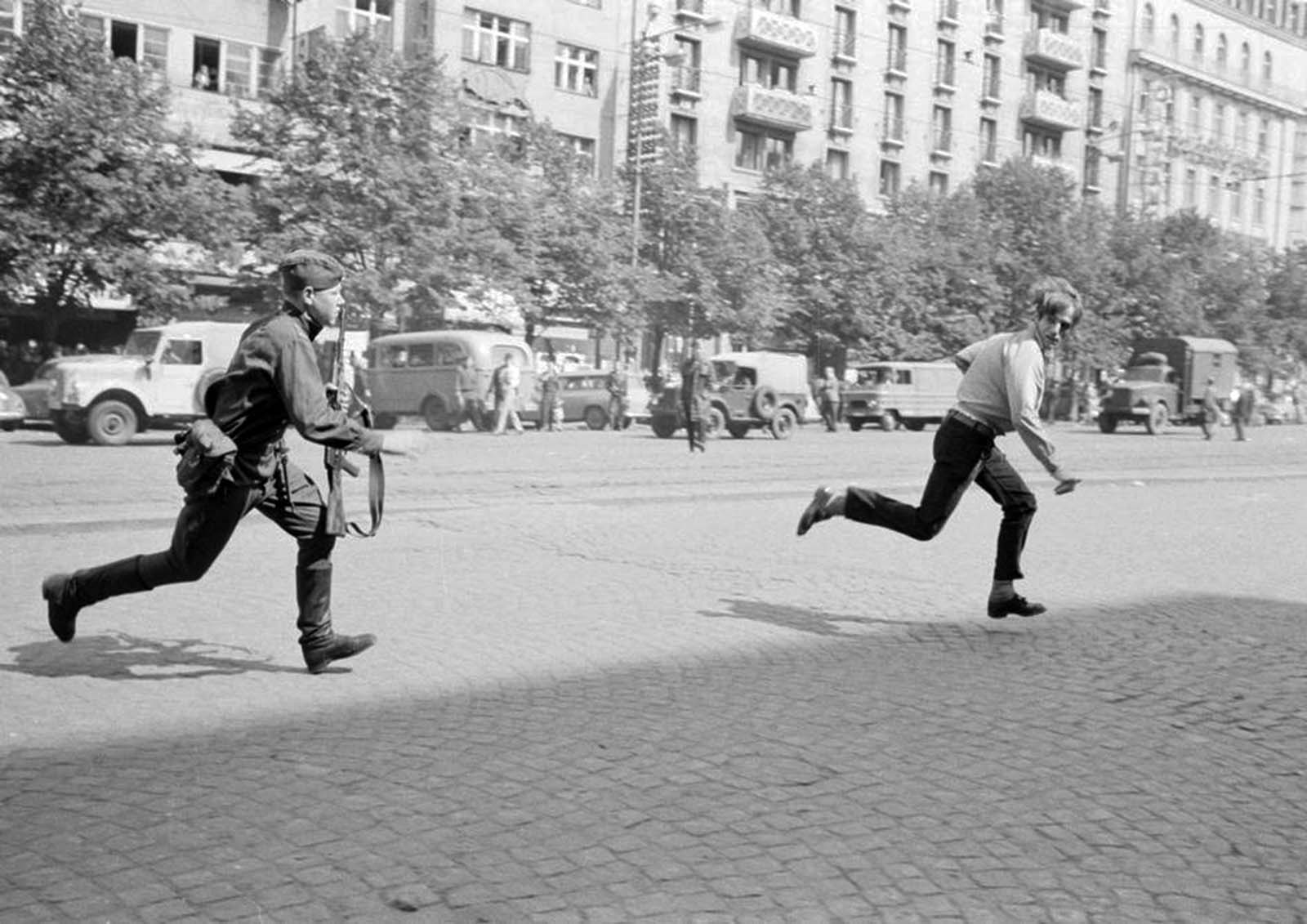 Soviet soldier chasing young man who had thrown stones at a tank, 1968.