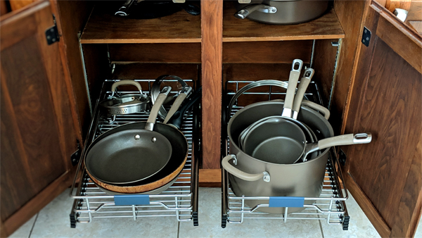 image of sliding organizers slid out of my kitchen cabinets, filled with pots and pans and lids