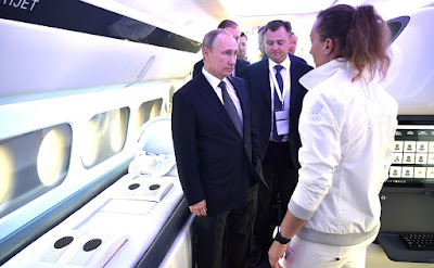 Vladimir Putin looks over a model of the Sukhoi SportJet interior at the International Aviation and Space Salon MAKS-2017.