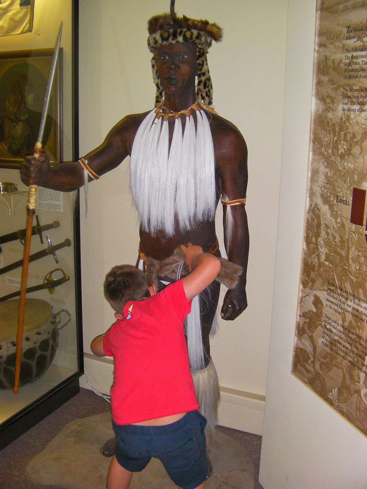 boy looking under grass skirt of museum exhibit