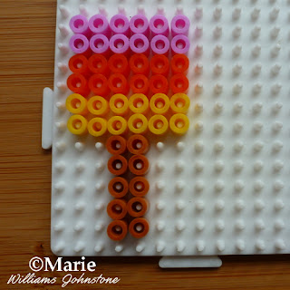 pink red yellow brown beads on white square board
