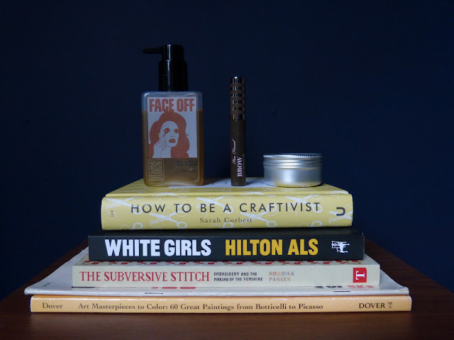 The picture shows a pile of books (from below to top: a colour book, a vintage magazine, The Subversive Stitch by Rozsika Parker, White Girls by Hilton Als and How To Be A Craftivist by Sarah Corbett. On top of the pile of books stands various makeup products. From left to right: Face Off Oil to Milk Cleanser by Neighbourhood Botanicals, Brow-Quickie Brush On Fibre Gel by Too Faced and Ultrabalm by Lush. The background is blue.