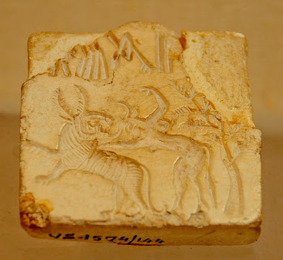 Mohenjo-Daro seal showing a zoomorphic horned female with horns, hooves and a tail, attacking a tiger.