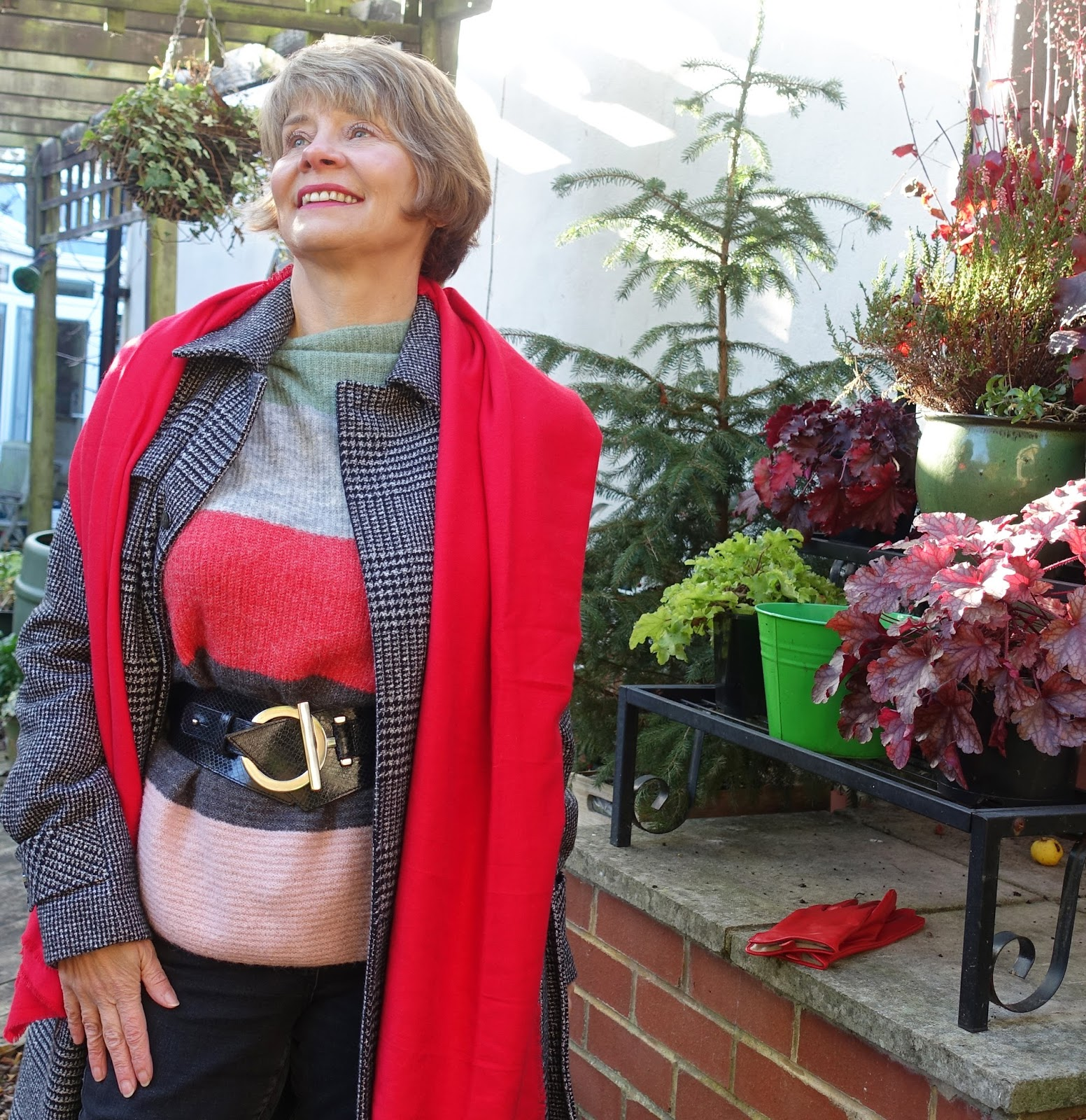 Image showing a smiling woman over the age of 50 wearing a striped winter jumper red scarf and check coat