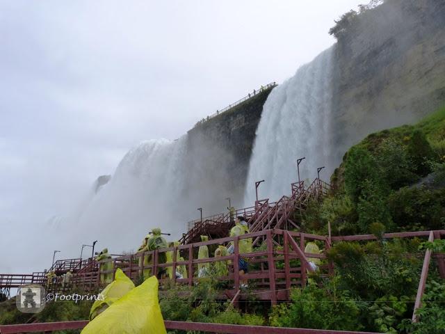 Ganz in gelb geht es nun ueber die roten Holzplanken, Richtung des Wasserfalls weiter. Je naeher wir kommen, desto lauter wird es und kurze Zeit spaeter wird es auch schon ziemlich schon nass.