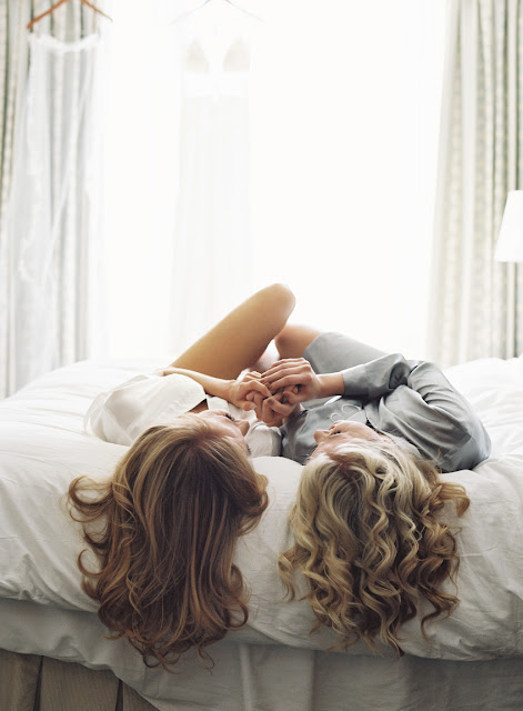 The bride and a bridesmaid share a happy moment on the bed | Karen Hill Photography