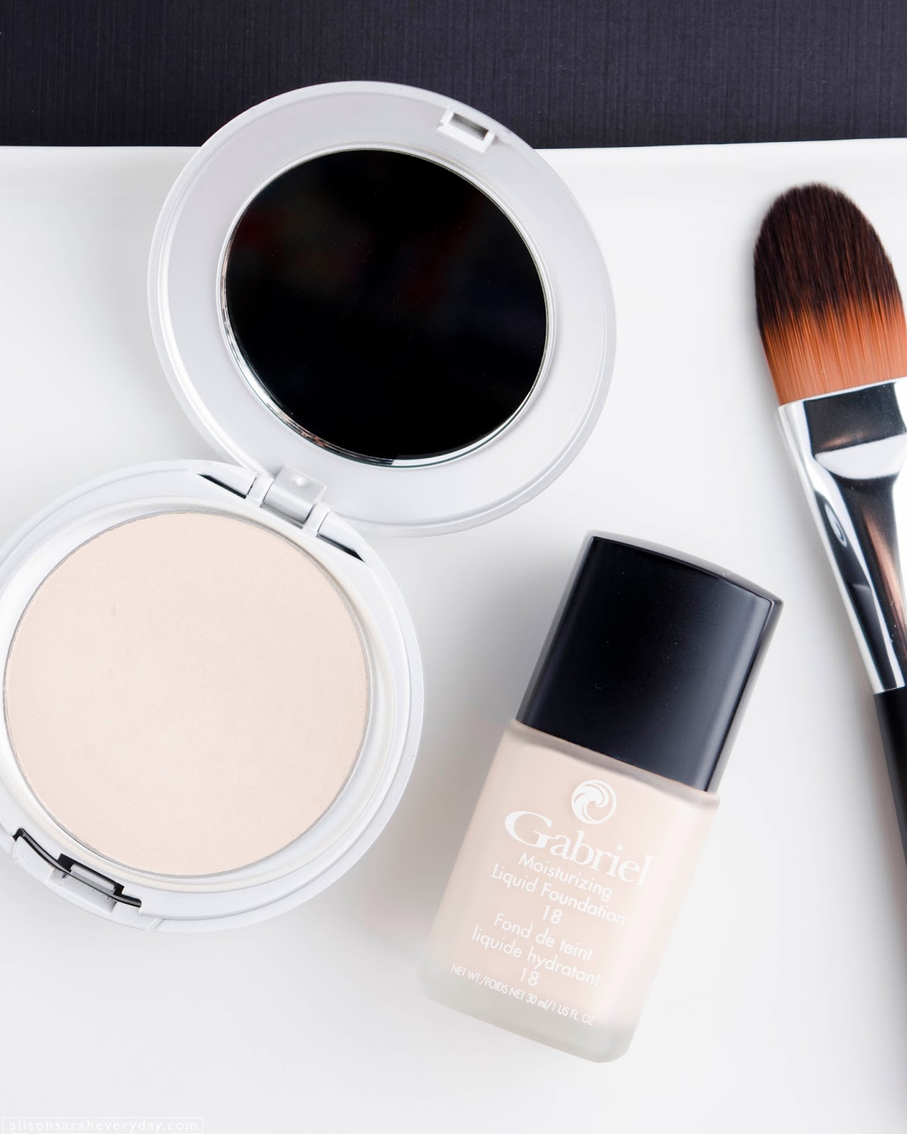 A flatlay image of Gabriel Cosmetics Liquid Foundation and Zuzu Luxe Powder Foundation