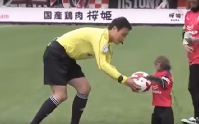 A monkey mascot dressed in full Cerezo Osaka kit hands over the match ball to referee Hiromu Kimura