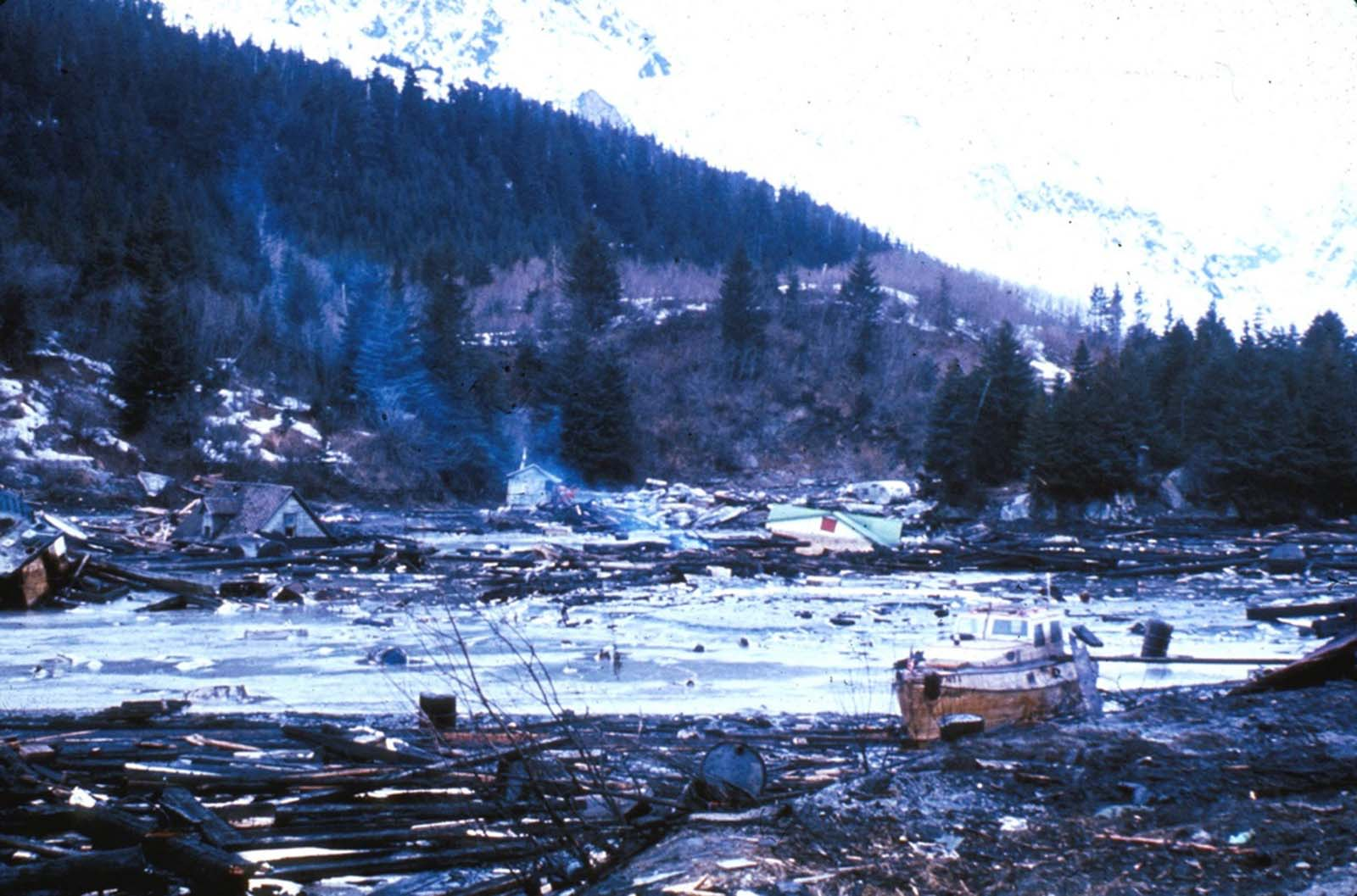 Tsunami damage and high-water line at Seward. The tsunami waves washed the snow from the lower slopes of the hillsides, and the height of the highest wave is marked by the sharp