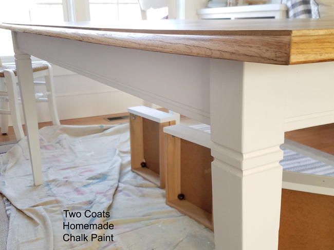 Farmhouse dining table with keeping drawers and tapering legs painted white.