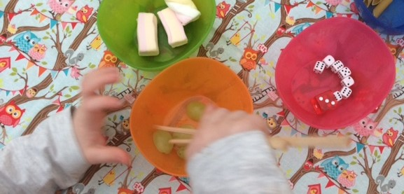 Chopsticks being used by a toddler