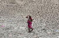 A women carries firewood as she walks through a dried-up portion of the Sabarmati river on a hot summer day in Ahmedabad, India, May 16, 2018. (Credit: Reuters/Amit Dave/File photo) Click to Enlarge.