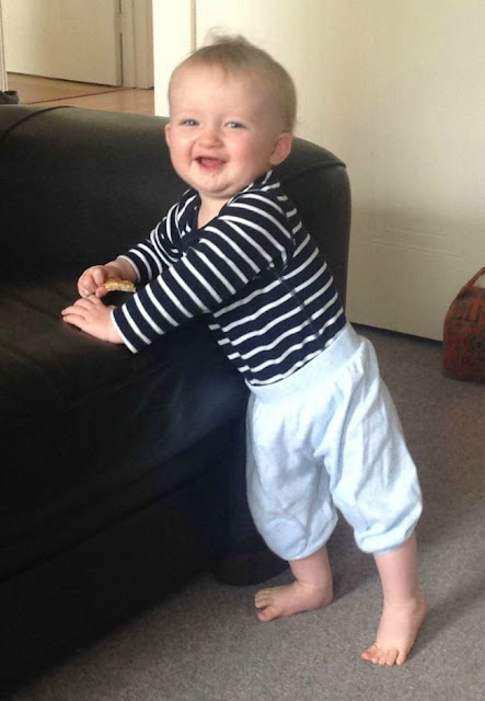 Baby standing against sofa toast in hand big smile on face