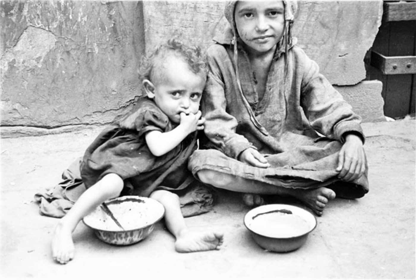Two children begging for food on the street.