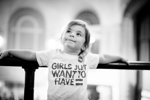 black and white image of a little girl who appears to be white at a Clinton rally, wearing a t-shirt that reads: 'Girls Just Want to Have [equal sign symbolizing the word equality]'