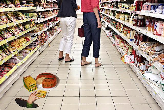 Yere düşmüş peynirlere yer altından uzanan bir el gösteren bir marketteki kaldırım sanatı resmi