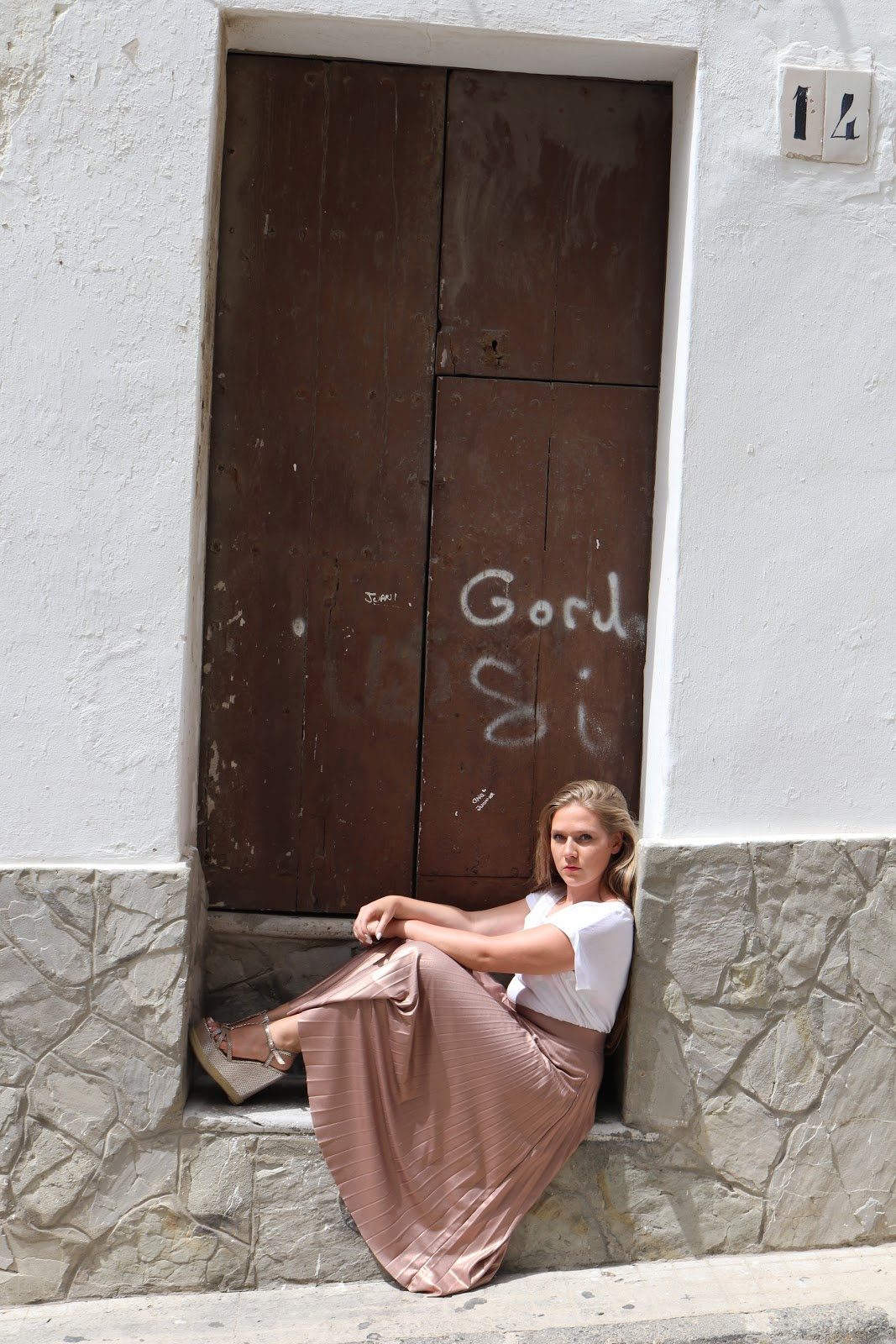 Blonde girl wearing metallic skirt sitting in a doorway in Tarifa, Spain